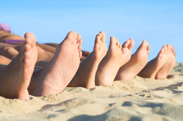 Close-up van voetenrij die in lijn bij zomerstrand liggen