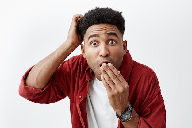 Close up van volwassen aantrekkelijke zwarthuidige man met afro kapsel in casual modieuze outfit kleding mond met hand, kijkend in de camera met geschokte uitdrukking na het horen van roddel over vriend.