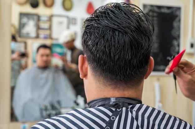 Close-up van volwassen mannen stijlvolle haarstylist knippen haar van klant in de kapper