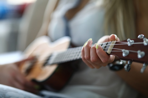 Close-up van volwassen persoon die akoestische gitaar houdt en melodie speelt. vrouwelijke hand die op koord wordt geplaatst. vrije tijd en vrije tijd. getalenteerde vrouw. muziek en hobby concept