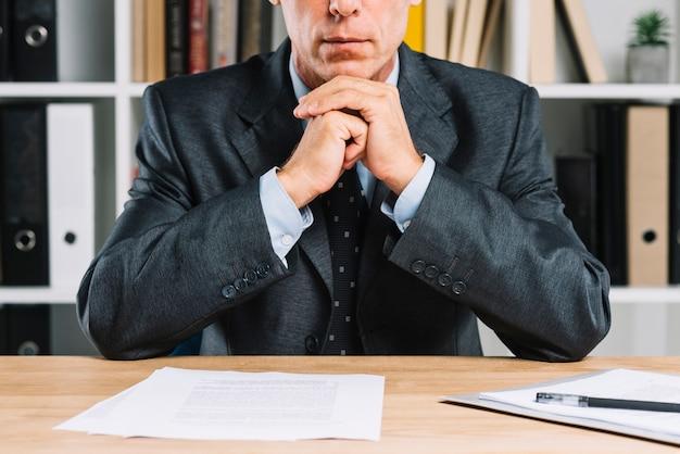 Close-up van volwassen zakenman met document papier op het bureau