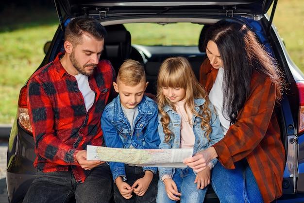Close up van vreugdevolle aangename familie die samen op vakantie gaan met tienerkinderen en de routekaart gebruiken om het juiste pad op de auto te kiezen