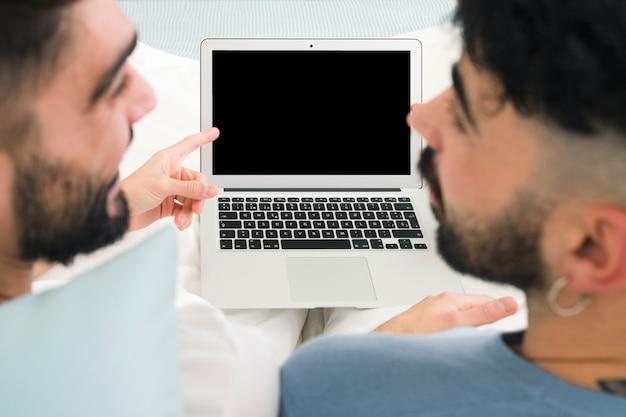 Close-up van vriend die de mens bekijkt die vinger over de laptop monitor richt