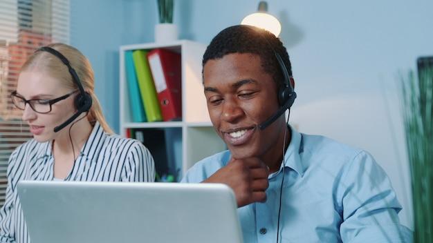 Close-up van vriendelijke afrikaanse man aan het werk in callcenter