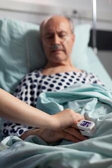 Close up van vriendelijke doktershanden die de hand van de patiënt vasthouden