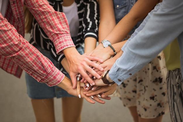 Close-up van vrienden die handen bovenop elkaar zetten