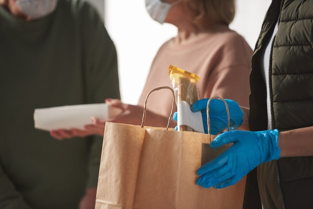 Close-up van vrijwilliger in beschermende handschoenen die met boodschappentas staat en voedsel voor senioren koopt