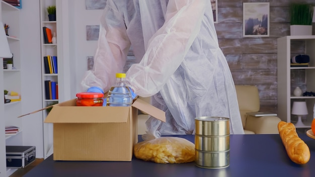 Close-up van vrijwilliger met handschoenen die voedsel inpakken en een beschermend pak dragen tegen coronavirus.
