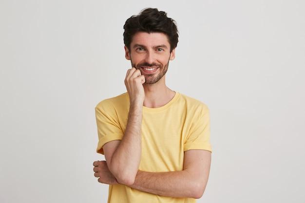 Close-up van vrolijke aantrekkelijke bebaarde jonge man draagt gele t-shirt ziet er zelfverzekerd uit en houdt gevouwen handen geïsoleerd op wit