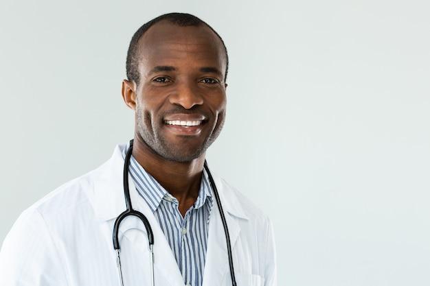 Close-up van vrolijke afro-amerikaanse arts die lacht terwijl hij klaar is om te werken