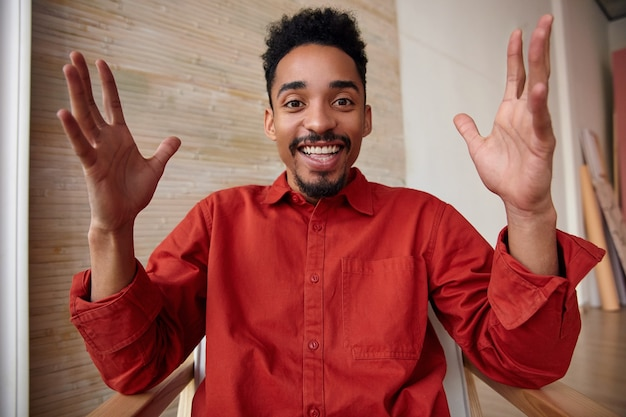 Close-up van vrolijke bebaarde donkerhuidige brunette man die zijn hand omhoog houdt terwijl hij vreugdevol kijkt met een brede glimlach, staande op beige interieur