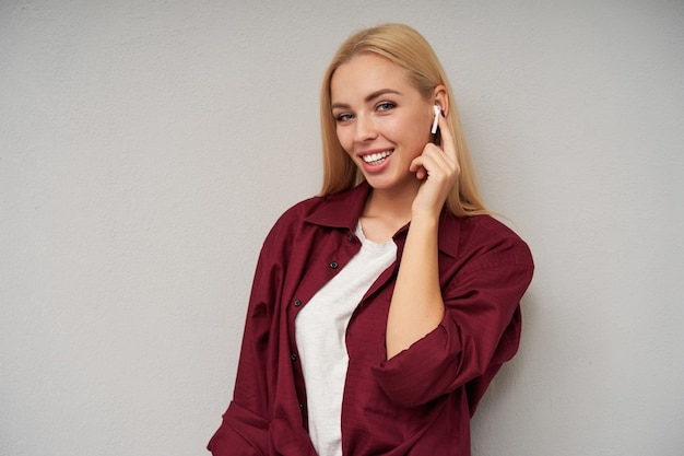 Close-up van vrolijke blauwogige mooie jonge vrouw met lang blond haar oortelefoons dragen en wijsvinger op oortje houden, breed glimlachend terwijl poseren over lichtgrijze achtergrond
