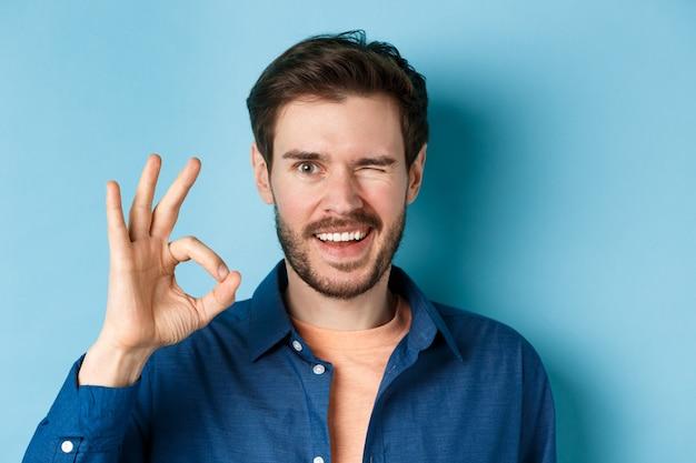 Close-up van vrolijke en zelfverzekerde bebaarde man verzekeren alles goed, ok gebaar tonen en knipogen, glimlachend in de camera, staande op een blauwe achtergrond.