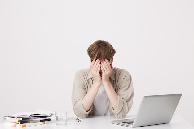 Close-up van vrolijke jonge mannelijke student met bretels draagt beige overhemd studie met behulp van laptopcomputer en notebooks zittend aan tafel geïsoleerd over witte muur