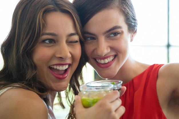 Close-up van vrolijke jonge vrouwen die dranken in restaurant roosteren