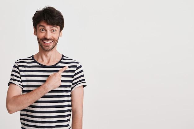 Close-up van vrolijke knappe jonge man met varkenshaar draagt gestreepte t-shirt voelt gelukkig geïsoleerd op wit
