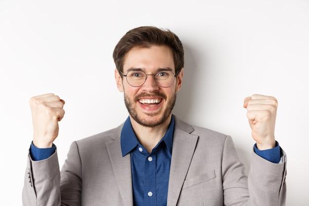 Close-up van vrolijke mannelijke ceo-manager in glazen en pak, ja zeggen en vieren winnen, vuist pomp maken, staande op een witte achtergrond.