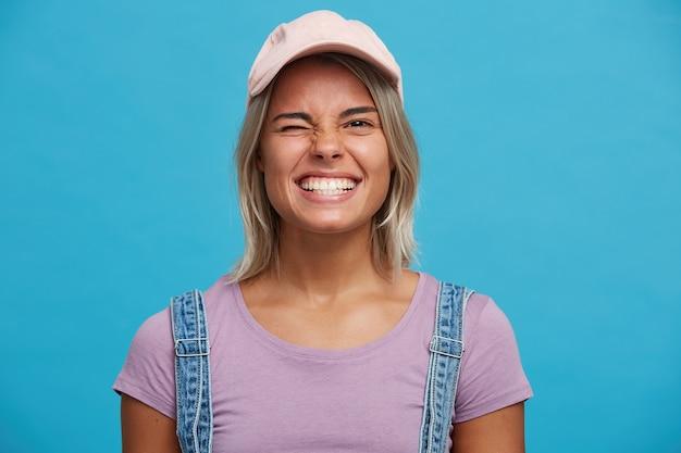 Close-up van vrolijke mooie blonde jonge vrouw draagt roze pet en violet t-shirt ziet er gelukkig uit, glimlachend en knipogen geïsoleerd over blauwe muur