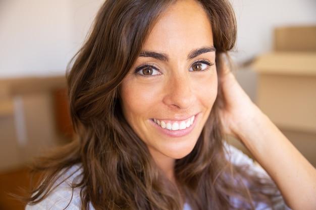 Close-up van vrolijke mooie jonge vrouw die zich in een nieuw appartement beweegt
