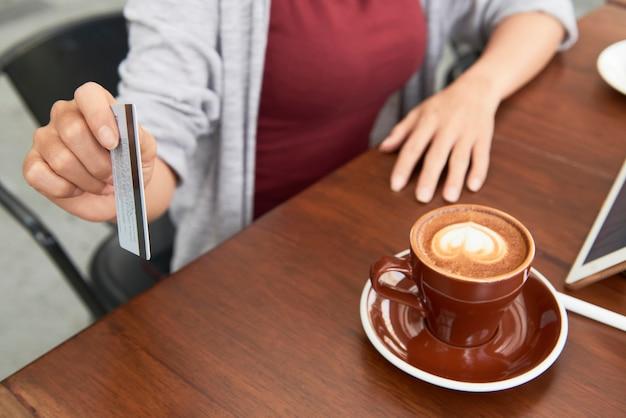 Close-up van vrouw betalen voor kopje koffie in café met creditcard