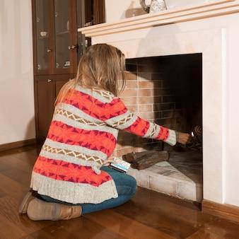 Close-up van vrouw brandende vuur in de open haard thuis