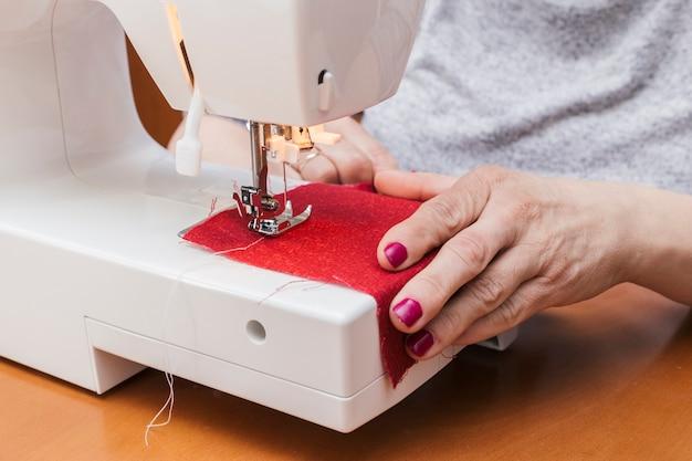 Close-up van vrouw die aan de naaimachine werkt