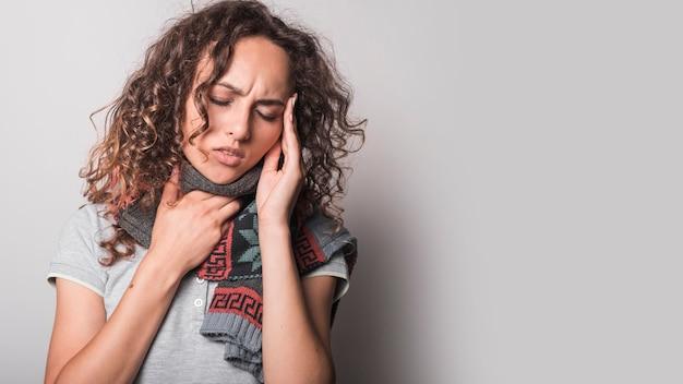 Close-up van vrouw die aan griep lijden die hoofdpijn hebben tegen grijze achtergrond