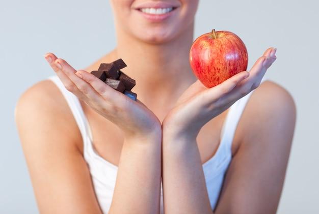 Close-up van vrouw die chocolade en appeldrank op chocolade en appel toont