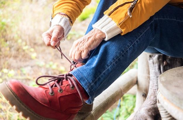 Close-up van vrouw die de veters van de laarsschoen bindt. vrouw geniet van wandelen en maakt zich klaar voor een excursie in de buitenlucht. rode laars en gele jas