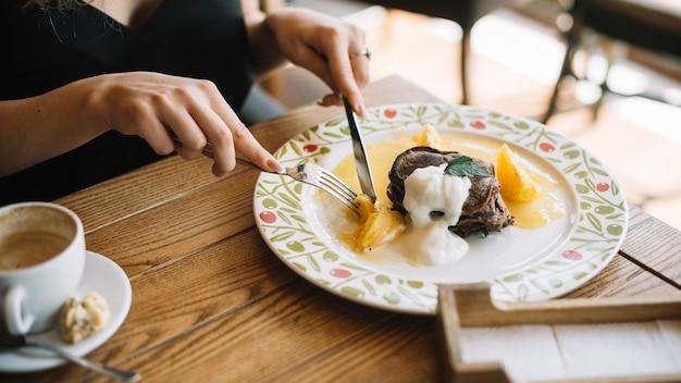 Close-up van vrouw die dessert met vork en botermes eet