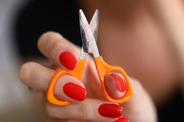 Close-up van vrouw die en kleine oranje schaar voor comfortabel kleermakerswerk houdt toont. apparatuur voor professionele naaister. werkende dingen. mode atelier concept