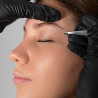 Close-up van vrouw die haar wenkbrauwen doet