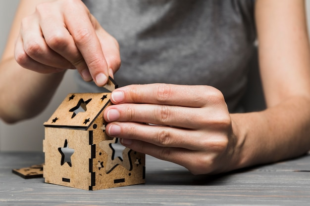 Close-up van vrouw die met de hand gemaakt huis op tafel