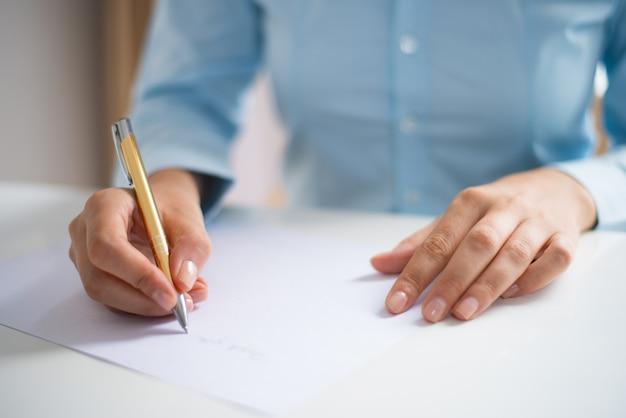 Close-up van vrouw die op blad van document schrijft