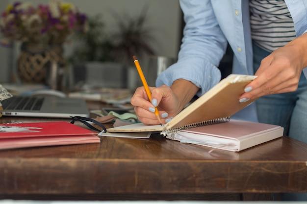 Close-up van vrouw die op notitieboekje schrijft