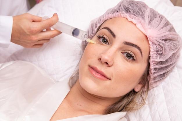 Close-up van vrouw die ozon op haar gezicht toepast voor cosmetische behandeling.