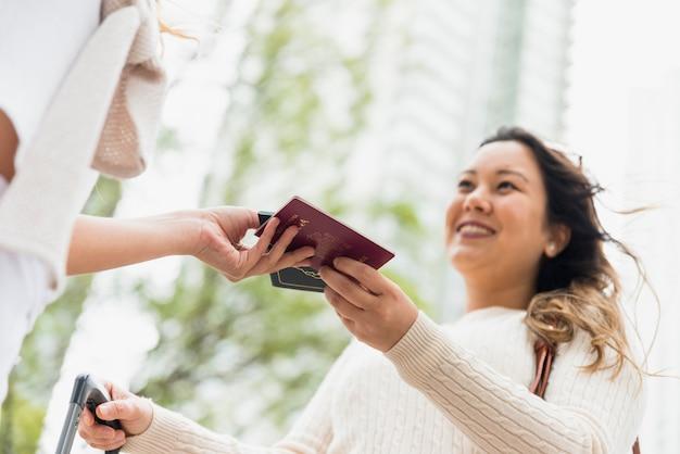 Close-up van vrouw die paspoort geeft aan haar vrouwelijke toeristenvriend in openlucht