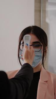 Close-up van vrouw die temperatuur meet met medische thermometer om covid 19 . te voorkomen