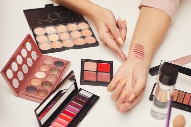 Close-up van vrouw die verschillende kleuren van oogschaduw op haar hand toont en raadpleegt over de decoratieve schoonheidsmiddelen