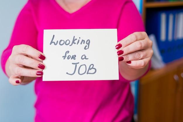 Close-up van vrouw die zich in bureaubinnenland bevindt met teken in handen.