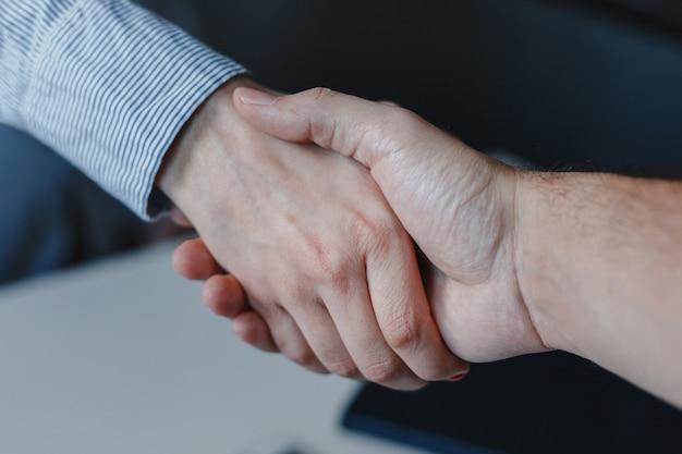 Close-up van vrouw en man zakelijke handdruk. handen bij elkaar.