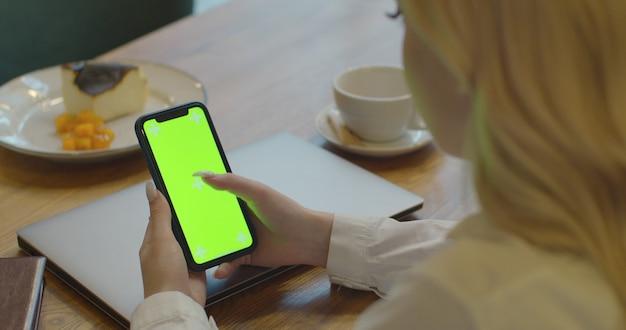 Close-up van vrouw hand houdt chroma key groen scherm met aan te raken.