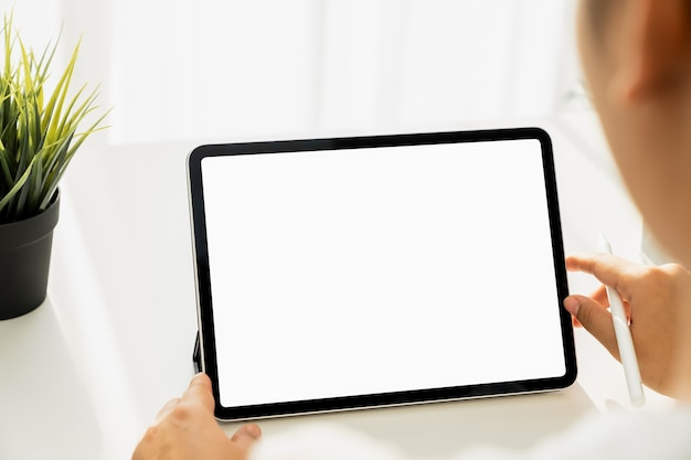 Close-up van vrouw hand met digitale tablet op tafel en het scherm is leeg.