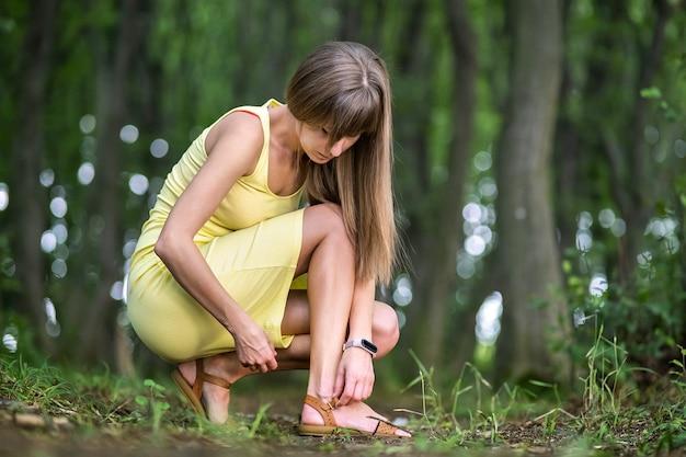 Close up van vrouw handen haar open zomer sandalen schoenen koppelverkoop in zomer park.