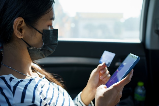 Close-up van vrouw handen met smartphone en creditcard zittend op de achterbank van de auto.