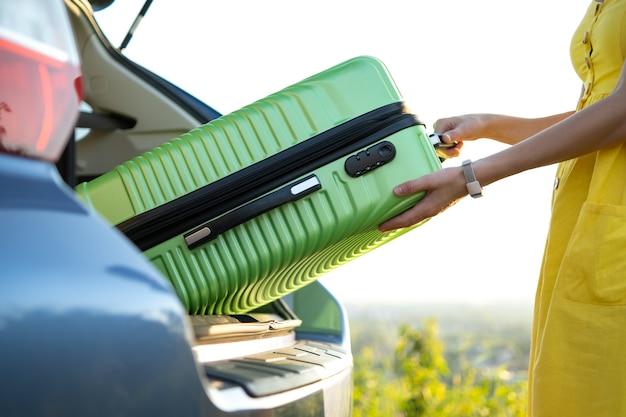 Close up van vrouw handen nemen groene koffer uit auto kofferbak. reizen en vakanties concept.