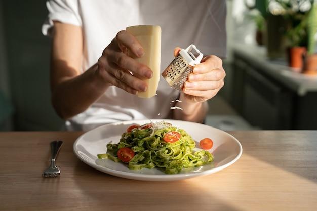 Close up van vrouw handen raspen parmezaanse kaas in pasta met pesto saus, verse kerstomaatjes, woonkamer op achtergrond.