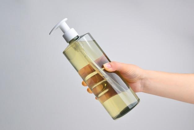 Close up van vrouw handen tonen sanitizer gel fles geïsoleerd op een witte ondergrond
