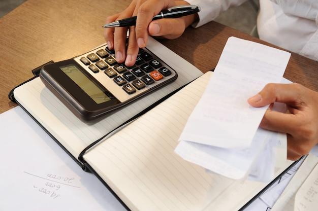 Close-up van vrouw het berekenen rekeningen op calculator