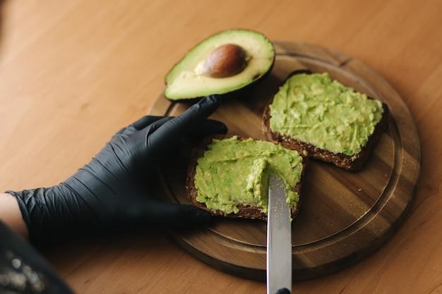 Close-up van vrouw in zwarte glowes zet guacamole of avocado uitgespreid bovenop roggebrood toast op een houten bord thuis. veganistisch ontbijt.